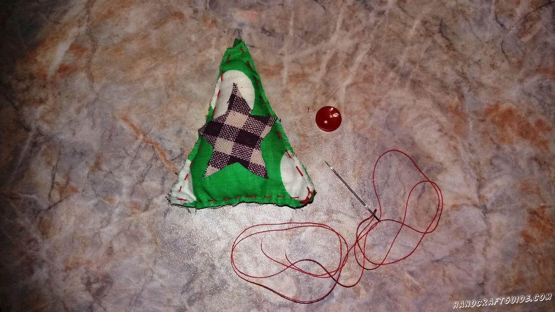 И закончим выполнение: сверху ёлочки мы пришьем пуговку, а снизу приклеиваем зубочистку. Осталось только прикрепить ниточку, чтоб можно было повесить нашу игрушку.