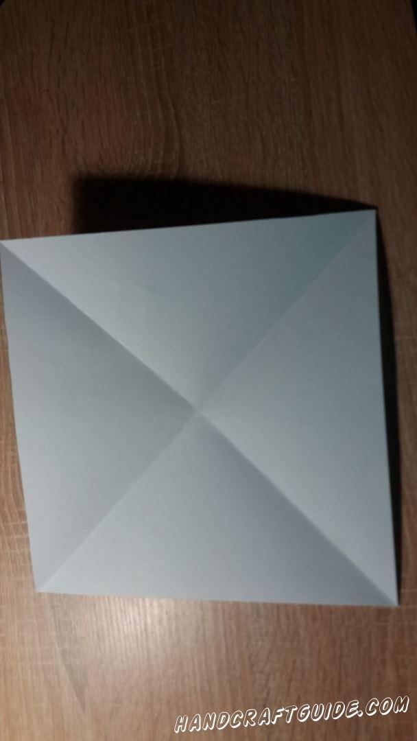 Для начала берем лист бумаги квадратной формы и складываем пополам в треугольник.