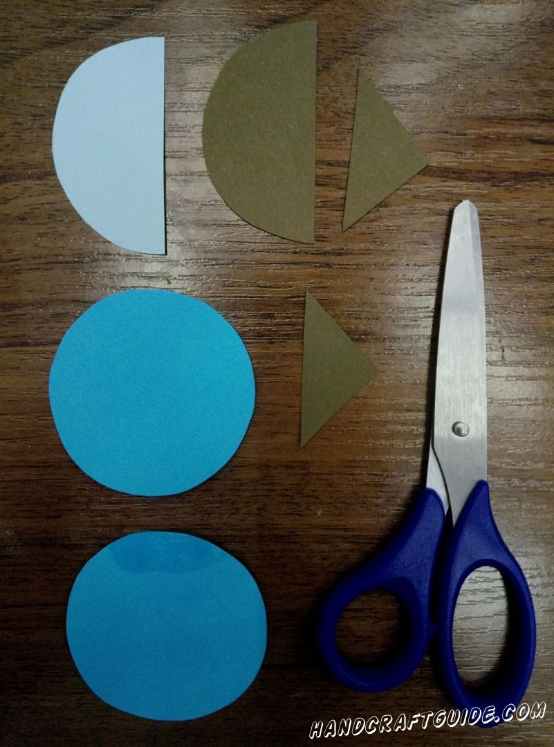 Cut out 2 circles of the same color (blue) and 2 more semi-circles of the same size in different colors. We also need 2 small triangles.