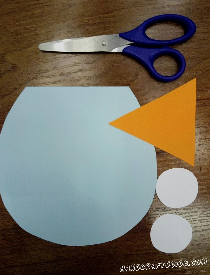 To start, we need to cut out a blue paper circle with one cropped side, an orange triangle and two white small circles