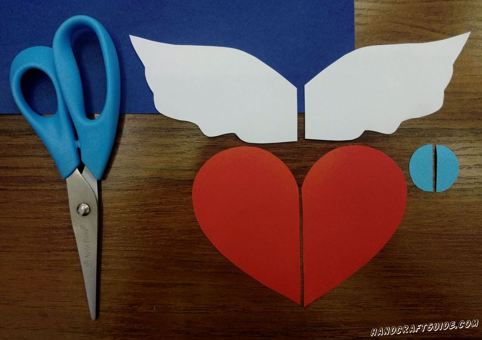 First cut out a large red heart and cut it in half. Then cut the wings out of white paper and also cut out a small blue circle and cut in half.