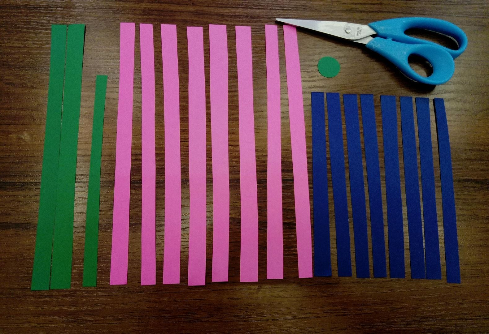 Let's begin from a very simple task, doing a lot of strips. Cut pink paper along into 8 identical strips. Cut horizontally 8 stripes out of the blue paper. Now take the green paper and cut out 2 long strips and one a bit shorter and a small circle. When everything is done, we can continue!