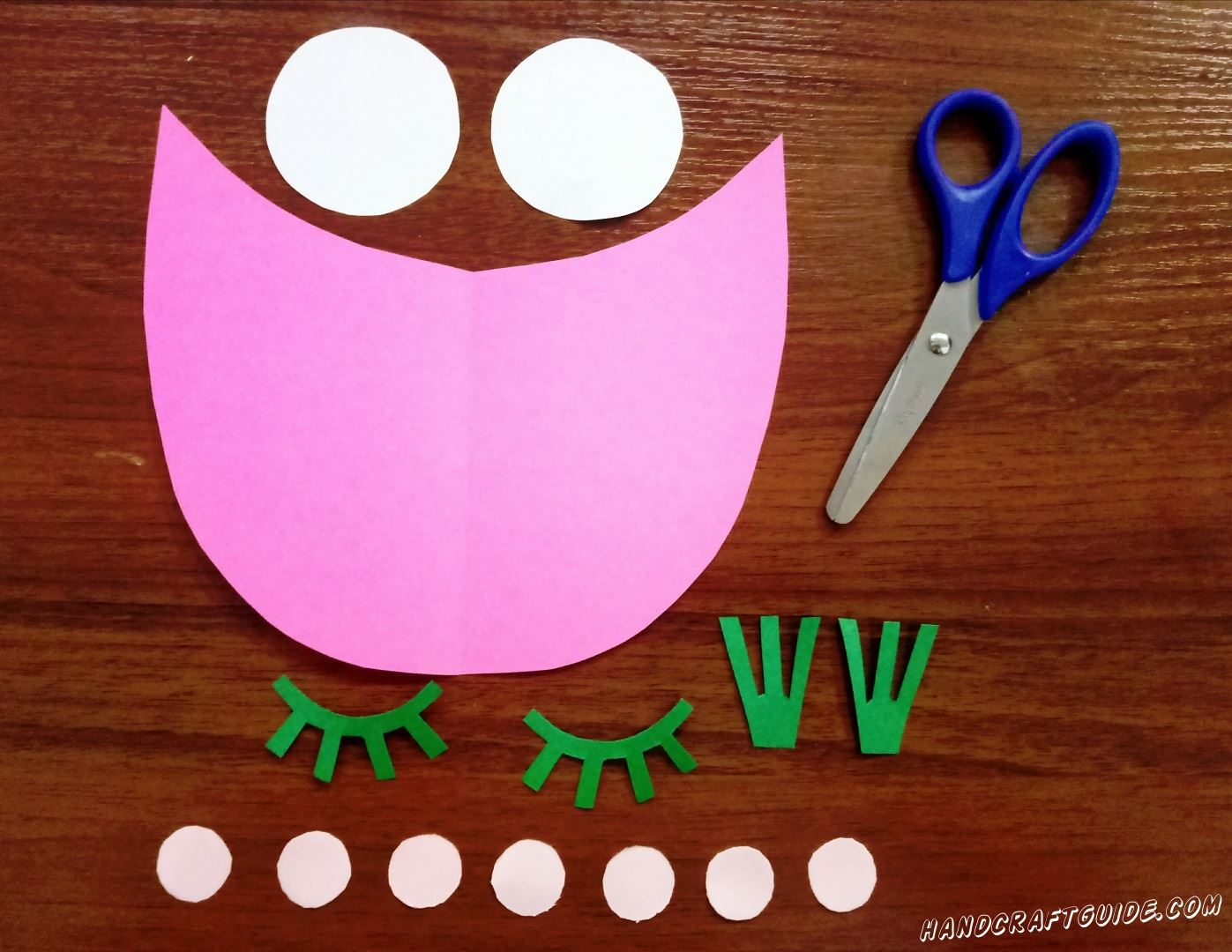 Take pink paper and scissors. Cut out a detail which looks like a boat or a wide smile :) Next take white paper and cut out 2 middle size circles and 7 small circles. Now choose green paper. Cut out eyeslashes and 2 details like crowns. Don't forget to cut a small orange rectangle. You can see how we did it in the photo :) Well done, let's continue...
