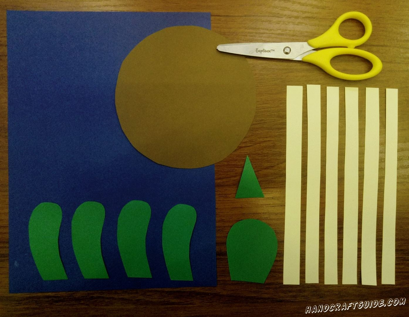 First take brown paper and cut out big circle. Then take green paper and cut out 4 details, short bent stripes with rounded edges on one side, which resemble paws. Do not postpone the green paper, because we need to cut out a small triangle and a detailresembling a balloon with a trimmed narrowed side. And finish with 6 identical stripes of yellow color. Well done, let's continue ...