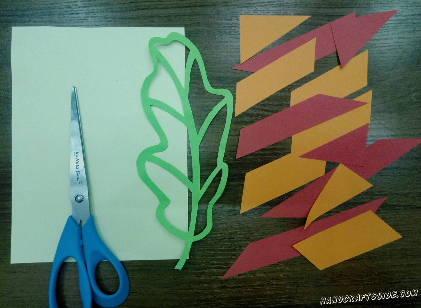 First, we need to cut out a green leaf, so that there is hole inside. The leaf should consist only of connected strips. If you can't do it with scissors, you can use an office knife. Next cut many different details of triangular and quadrangular shapes out of orange and red paper.
