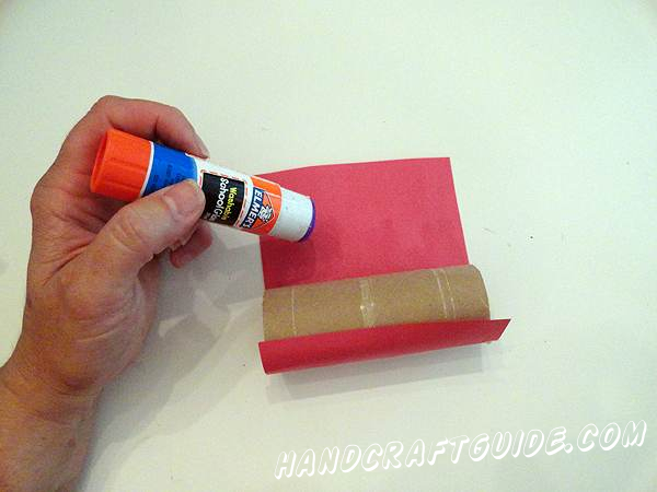 Start gluing flatly a leave on the one of the ends of cardboard tube. *If you want you can do the following as the first step: at first you glue the cardboard cylinders over with the construction paper or it is possible that you make the both with construction paper and without it.