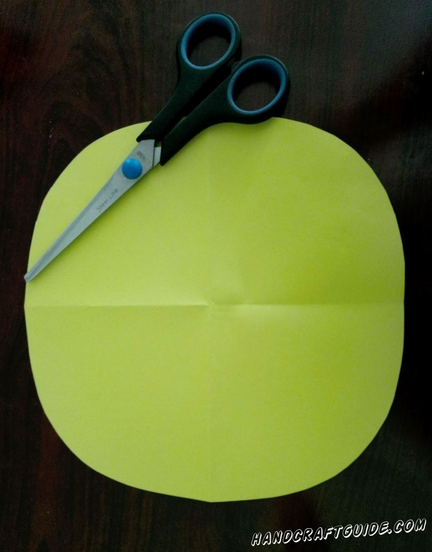 To start, cut out a circle of yellow paper.