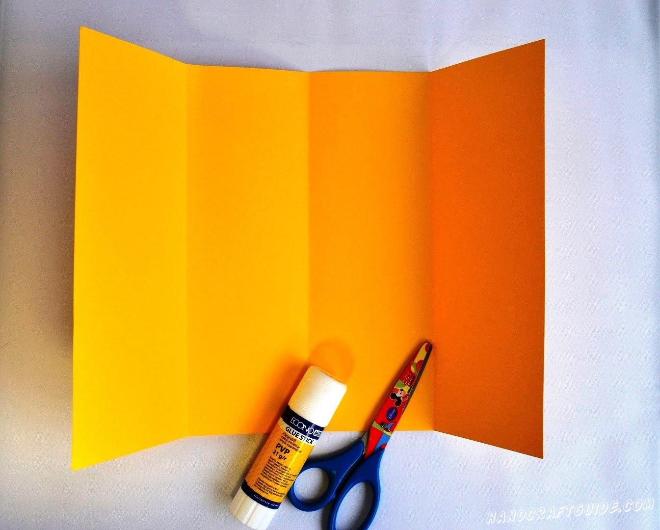 Берем лист цветной бумаги или картона и сгибаем его на 4 одинаковые полоски, разворачиваем нашу заготовку.
