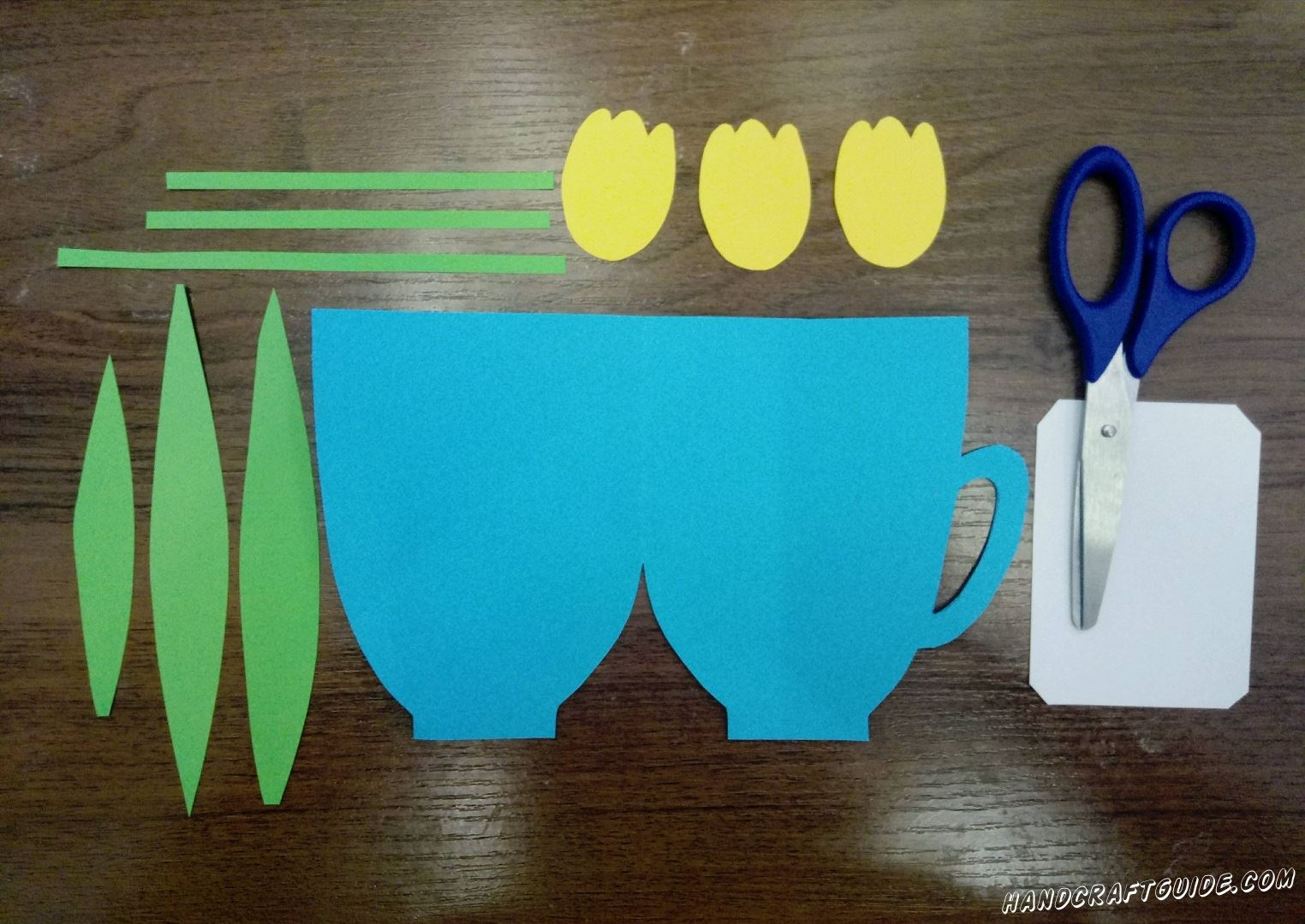 From the blue cardboard folded in half, cut out the shape of the cup. Then all the necessary details of colored paper, as in the photo.