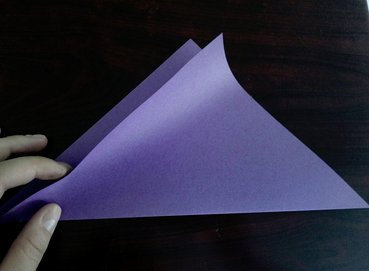 We bend, a sheet of paper of the square form, on a diagonal in half. Bend the folded sheet once again in half, just quite lightly, solely for charting the middle line. So it will be easier for you to make the cat's face symmetrical in the future.