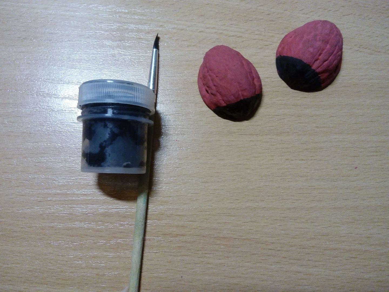 Затем берем черную краску и закрашиваем небольшую часть на скорлупе, это личико наших жучков