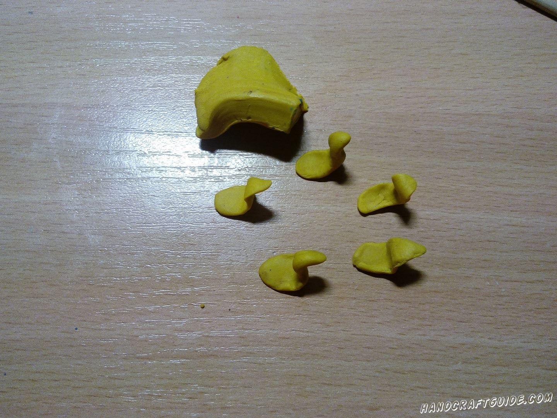 Затем берем желтый пластилин и лепим 5 фигурок, напоминающих уток плывущих в реке, только плоской формы.
