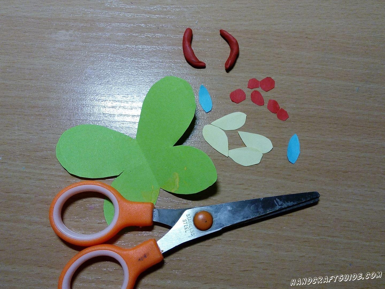 Затем берем бумагу зелёного цвета и вырезаем деталь в форме крыльев бабочки. Также врезаем 4 детали в форме семечки желтого цвета , 2 голубых овала и 6 небольших кружочков. Переходим к пластилину и лепим 2 небольшие дуги