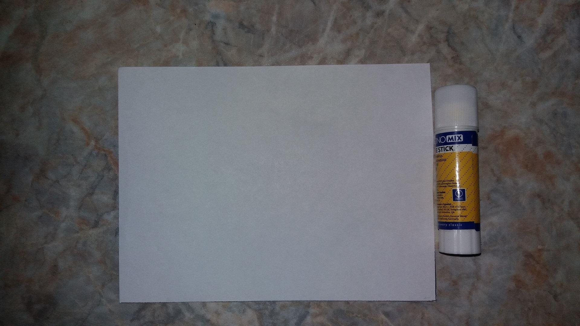 Затем берем листик белой бумаги и скручиваем его в трубку, в таком положении и склеиваем