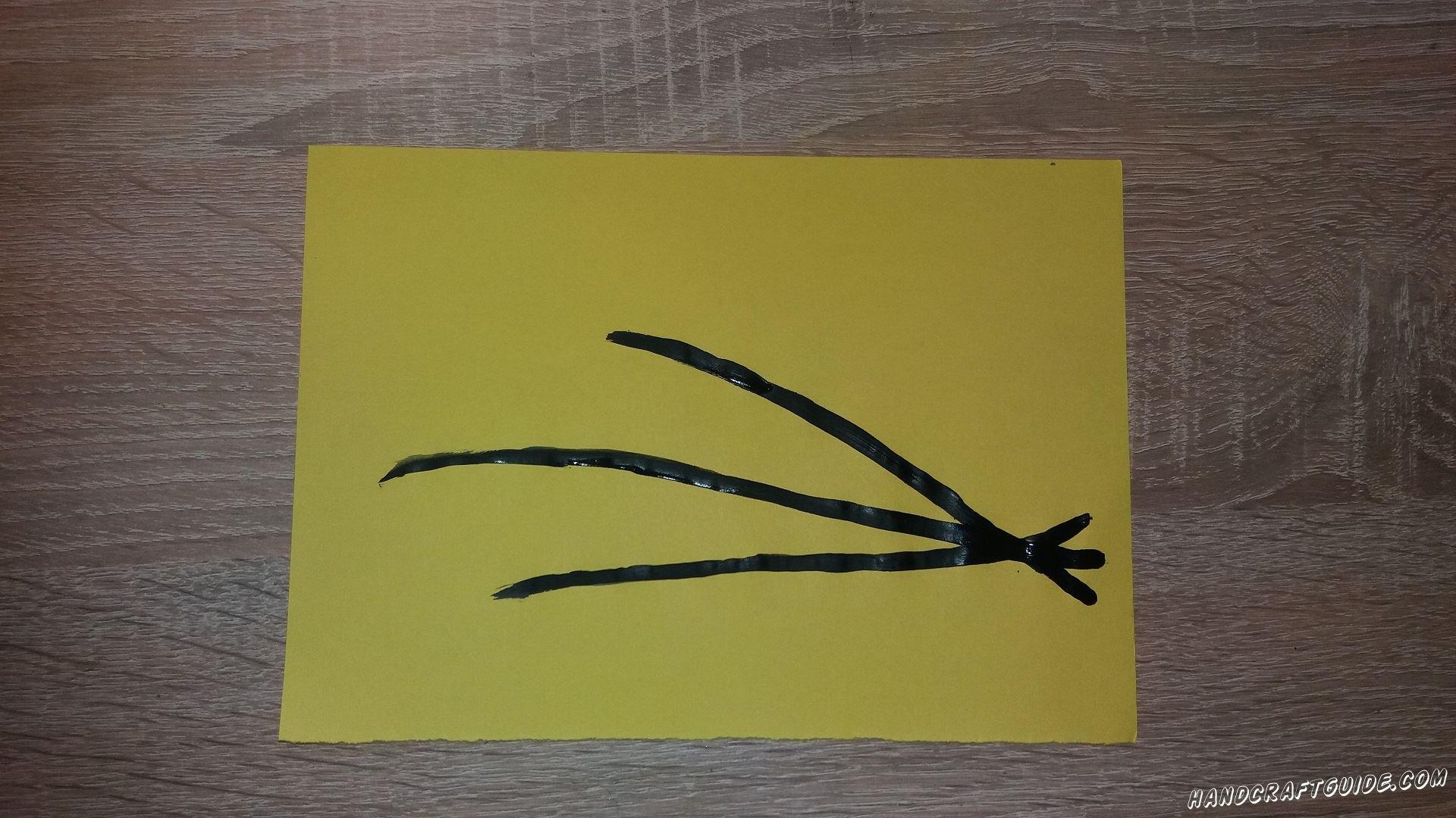 Берем чёрную краску и рисуем 3 веточки на желтом листе бумаги.