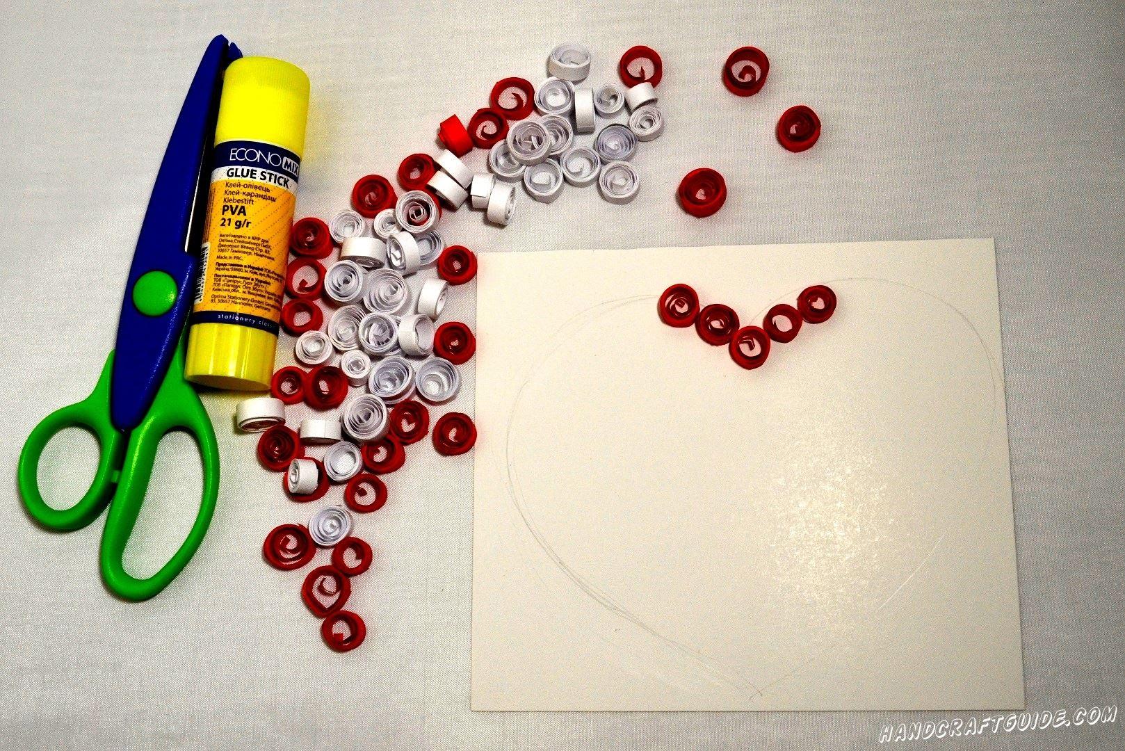 Затем берем лист картона и вырезаем ровный квадрат. Это будет фон нашей картины. Цвет фона можете выбрать абсолютно свободно. Теперь берем красные кружки и наклеиваем на фон, в форме контура сердечка.