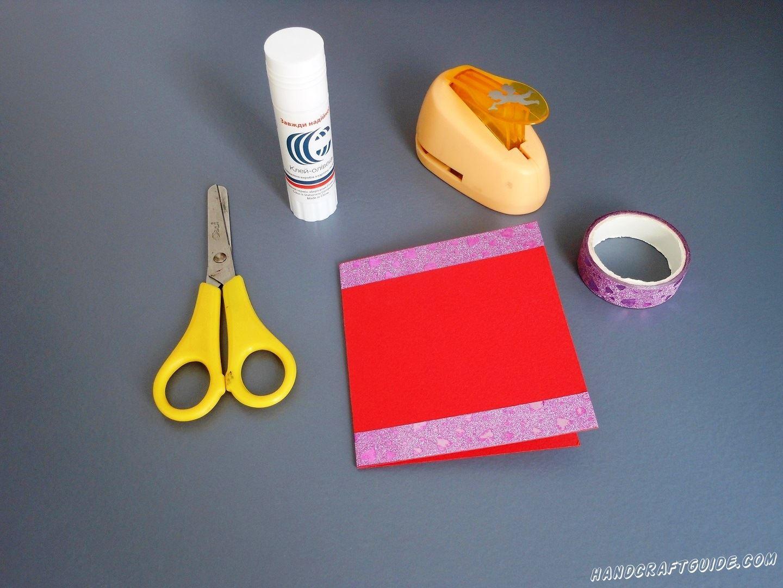 Берем красный лист бумаги и складываем его пополам, в форму книжечки. Снизу и сверху внешней стороны мы приклеиваем по полоске цветного скотча
