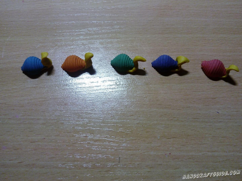К каждой такой пластилиновой детальке мы крепим по 1 макаронине, ни нижнюю плоскую часть. Получаются улитки с панцирями.