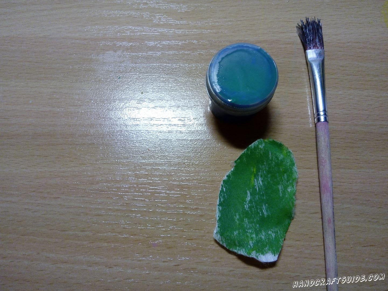 Далее мы берем один ватный диск и обрезаем два края, делая листочек. Закрашиваем его зеленым цветом.