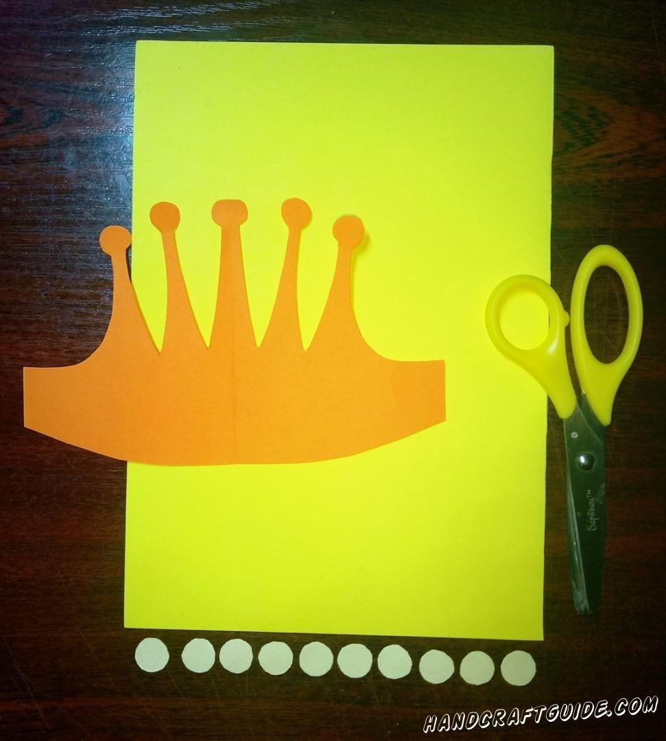 Вырезаем бумажную корону оранжевого цвета, а также десять маленьких светло-голубых кружков. Важно использовать плотную бумагу в этой поделке.