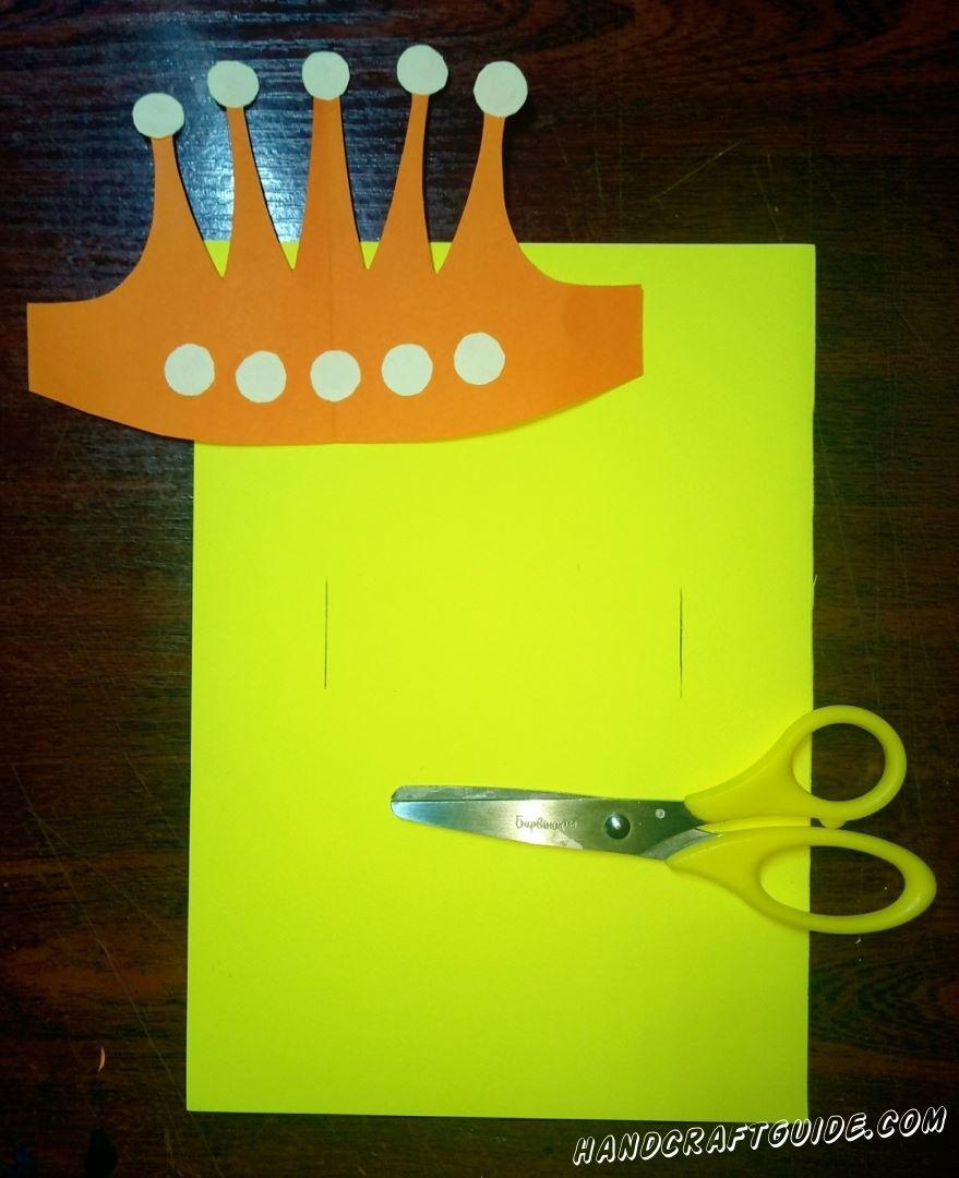 На плотном желтом листе бумаги мы делаем два надреза, напротив друг друга.