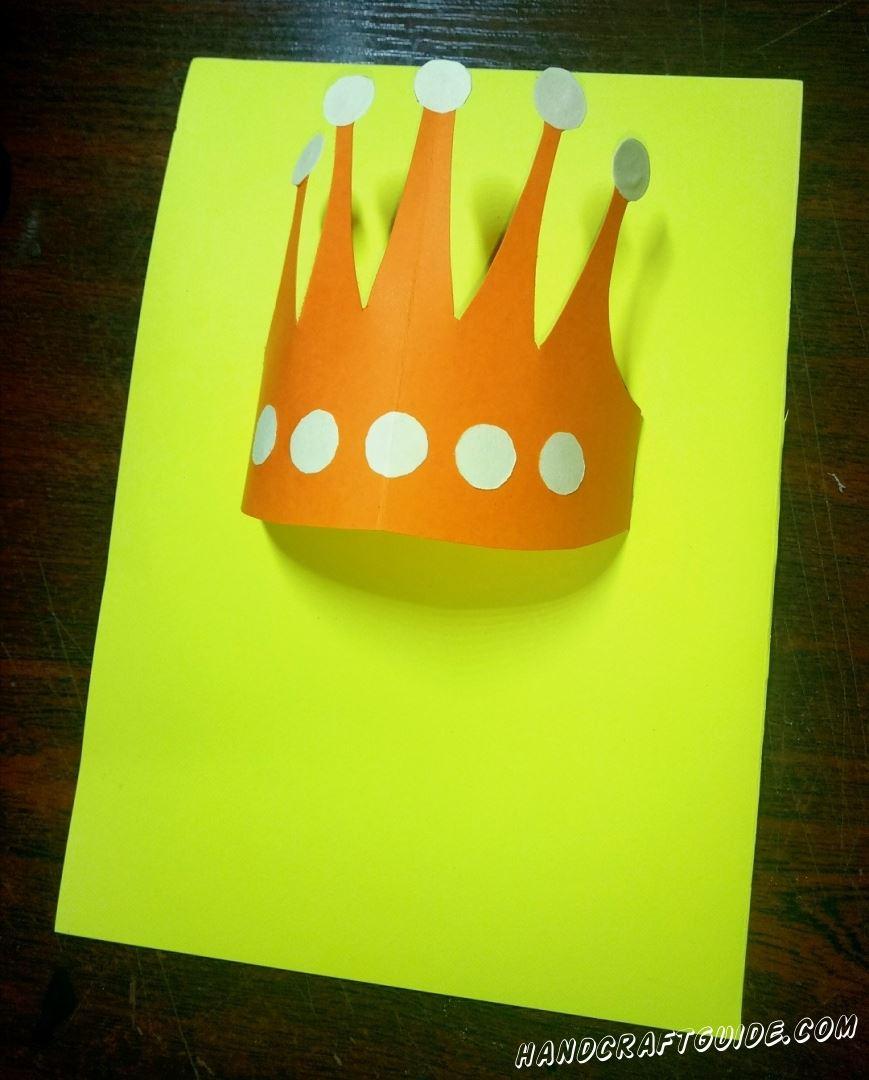 Вставляем края короны в надрезы желтой бумаги.